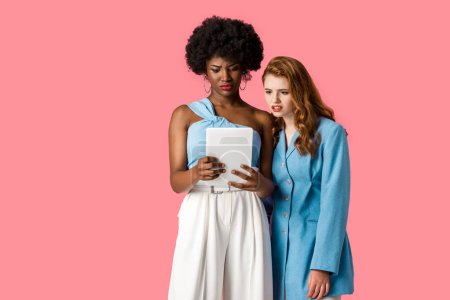 Photo for Displeased multicultural girls looking at digital tablet isolated on pink - Royalty Free Image