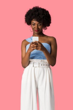happy african american girl using smartphone isolated on pink