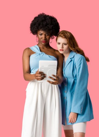 Photo for Displeased multicultural women looking at digital tablet isolated on pink - Royalty Free Image