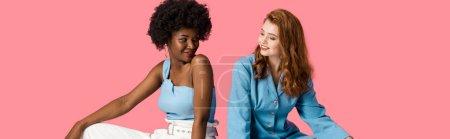 Photo pour Tir panoramique de femmes multiculturelles gaies regardant les uns les autres isolés sur le rose - image libre de droit