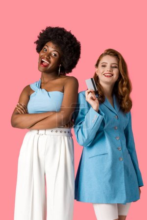 Photo for Cheerful redhead girl holding credit card near african american woman standing with crossed arms isolated on pink - Royalty Free Image