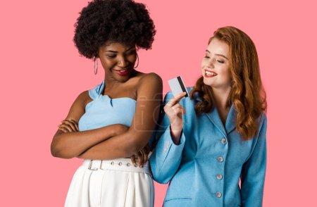 Photo pour Joyeuse rousse fille tenant carte de crédit près souriant afro-américaine debout avec les bras croisés isolé sur rose - image libre de droit