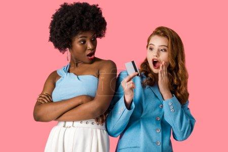 Photo pour Surprise rousse fille tenant carte de crédit près choqué afro-américaine debout avec les bras croisés isolé sur rose - image libre de droit