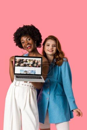 Photo pour Kiev, Ukraine - 9 août 2019: les filles multiculturelles gaies souriant près de l'ordinateur portable avec site depositphotos sur l'écran isolé sur le rose - image libre de droit