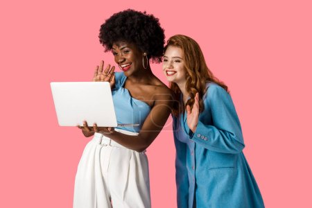 Photo for Happy multicultural girls waving hands while having video call isolated on pink - Royalty Free Image