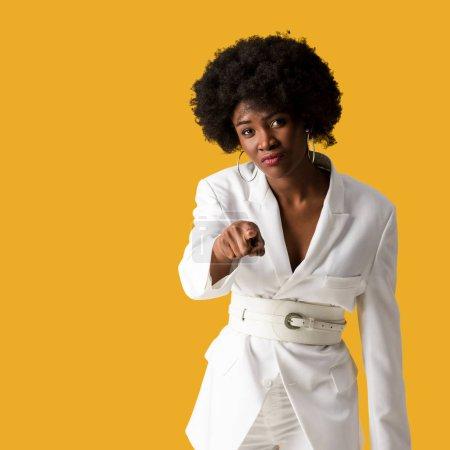Photo pour Foyer sélectif de la femme afro-américaine bouclée pointant avec le doigt isolé sur orange - image libre de droit