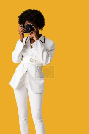 Photo for Curly african american woman covering face while taking photo isolated on orange - Royalty Free Image