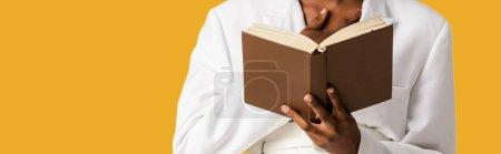 Photo pour Plan panoramique de femme afro-américaine tenant livre isolé sur orange - image libre de droit