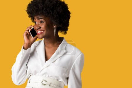 Photo for Cheerful and curly african american woman talking on smartphone isolated on orange - Royalty Free Image