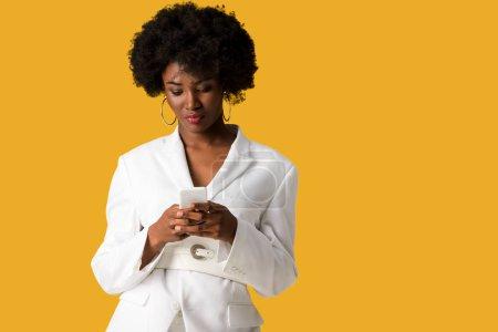 Photo pour Belle femme afro-américaine bouclée utilisant le smartphone isolé sur l'orange - image libre de droit