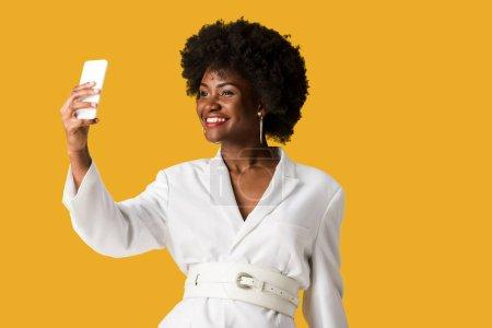 Photo pour Femme américaine africaine de sourire prenant le selfie d'orange - image libre de droit