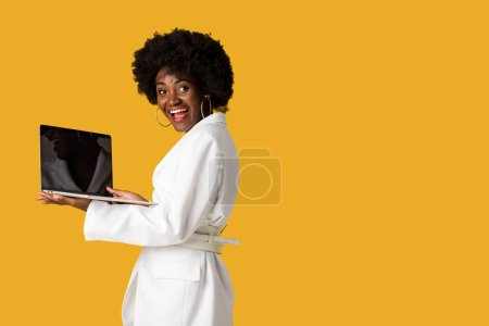 Photo for Excited african american girl holding laptop with blank screen isolated on orange - Royalty Free Image