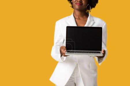 vue recadrée de heureuse fille afro-américaine tenant ordinateur portable avec écran vide isolé sur orange