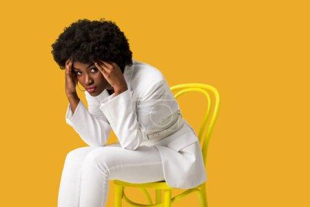 Photo pour Fille américaine africaine fatiguée s'asseyant sur la présidence jaune d'isolement sur l'orange - image libre de droit