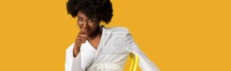 Photo for Panoramic shot of african american woman sitting on yellow chair and pointing with finger isolated on orange - Royalty Free Image