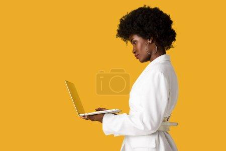 Photo pour Vue latérale de la fille américaine africaine utilisant l'ordinateur portatif d'isolement sur l'orange - image libre de droit