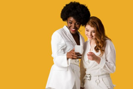 Photo for Happy multicultural girls looking at smartphone isolated on orange - Royalty Free Image