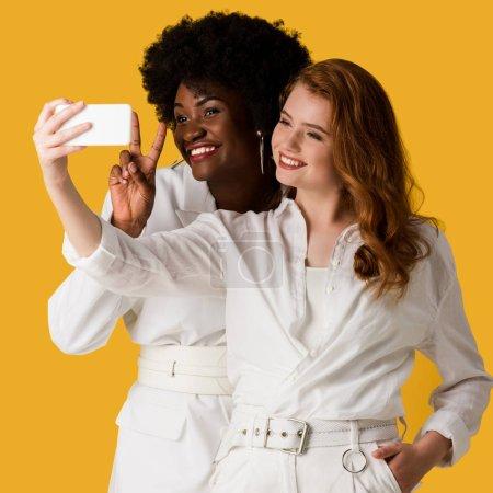 Photo pour Filles multiculturelles heureuses prenant le selfie d'isolement sur l'orange - image libre de droit