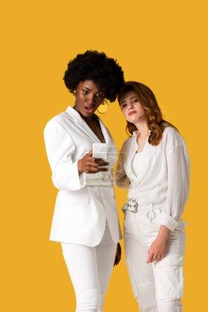 Photo pour Femme afro-américaine choquée regardant le smartphone près de la fille rousse d'isolement sur l'orange - image libre de droit