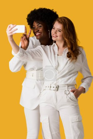 Photo for Smiling multicultural girls taking selfie isolated on orange - Royalty Free Image