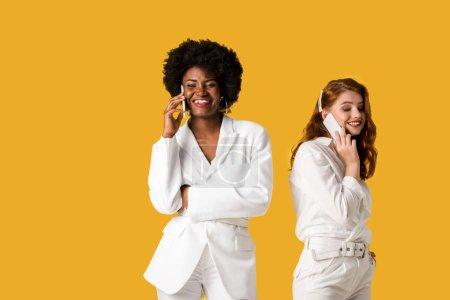 Photo pour Filles multiculturelles heureuses parlant sur des smartphones tout en restant isolé sur l'orange - image libre de droit