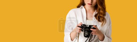 Photo for Panoramic shot of redhead girl holding digital camera isolated on orange - Royalty Free Image