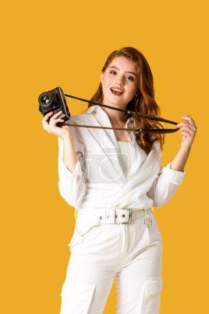 Photo for Cheerful redhead girl holding digital camera isolated on orange - Royalty Free Image