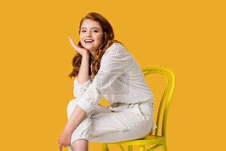 Photo pour Fille heureuse de rousse s'asseyant sur la présidence jaune d'isolement sur l'orange - image libre de droit