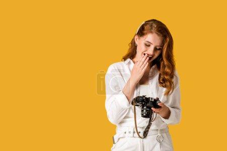 Photo pour Fille heureuse de rousse retenant l'appareil-photo numérique d'isolement sur l'orange - image libre de droit