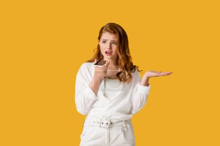 Photo for Dissatisfied redhead girl holding smartphone and gesturing isolated on orange - Royalty Free Image