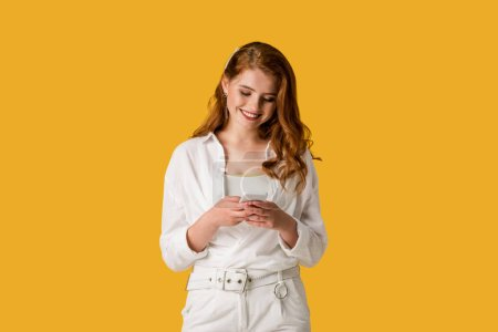 Photo for Happy redhead girl using smartphone and smiling isolated on orange - Royalty Free Image