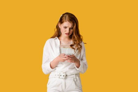 Photo for Sad redhead woman using smartphone isolated on orange - Royalty Free Image