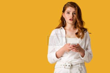 Photo pour Femme rousse surprise utilisant le smartphone isolé sur l'orange - image libre de droit