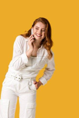 Photo pour Femme heureuse de rousse parlant sur le smartphone d'isolement sur l'orange - image libre de droit