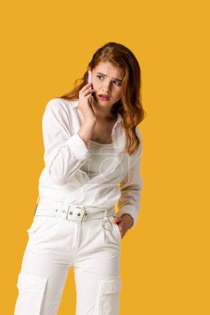Photo pour Femme rousse choqué parler sur smartphone isolé sur orange - image libre de droit