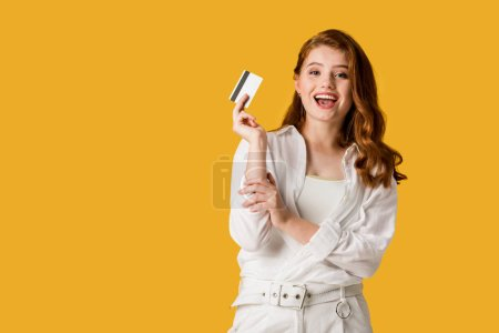 Photo for Excited young woman holding credit card isolated on orange - Royalty Free Image