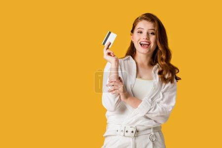 Foto de Mujer joven excitada sosteniendo tarjeta de crédito aislada en naranja - Imagen libre de derechos