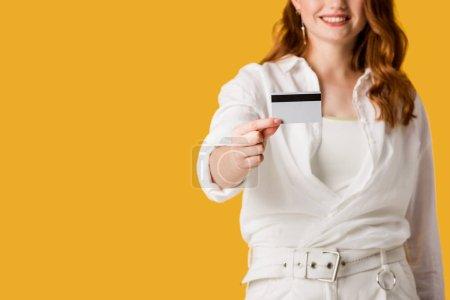 Photo pour Vue recadrée de fille heureuse de rousse retenant la carte de crédit d'isolement sur l'orange - image libre de droit
