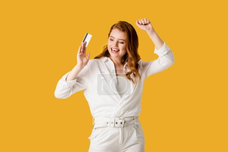 Photo for Cheerful redhead girl gesturing while holding credit card isolated on orange - Royalty Free Image