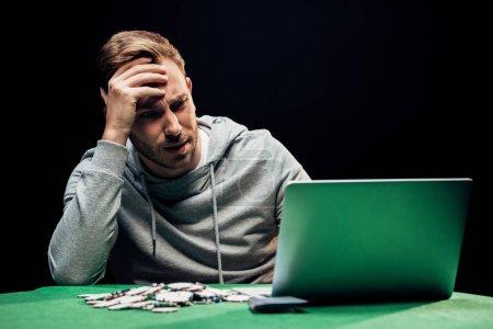 Photo pour Foyer sélectif de l'homme frustré regardant ordinateur portable près de jetons de poker - image libre de droit