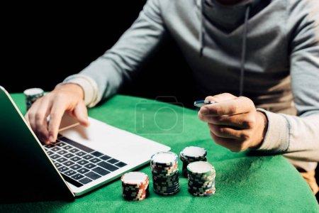 Photo pour Vue recadrée de l'homme retenant la pièce de poker et tapant sur l'ordinateur portatif isolé sur le noir - image libre de droit