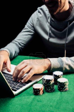 Photo pour Vue recadrée de l'homme heureux tapant sur l'ordinateur portatif près des jetons de poker d'isolement sur le noir - image libre de droit