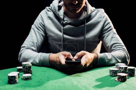 Photo pour Vue recadrée de l'homme retenant le smartphone avec l'écran blanc près des puces de poker d'isolement sur le noir - image libre de droit