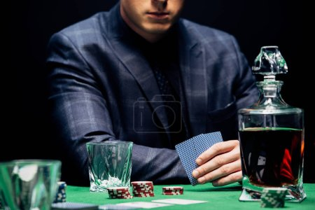 Photo pour Kyiv, Ukraine - August 20, 2019 : cropped view of man holding playing cards near poker chips isolated on black - image libre de droit