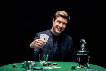 Photo pour KYIV, UKRAINE - AUGUST 20, 2019: selective focus of happy man holding playing cards near alcohol drink isolated on black - image libre de droit