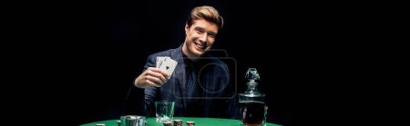 Photo pour Kyiv, Ukraine - 20 août 2019 : photo panoramique d'un homme heureux tenant des cartes à jouer près d'une boisson alcoolisée isolé sur un noir - image libre de droit