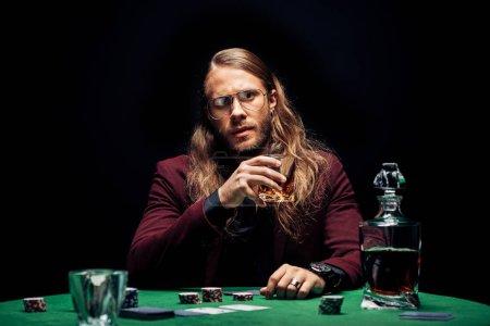 Foto de Enfoque selectivo del hombre en gafas cerca de las cartas de juego aislado en negro - Imagen libre de derechos