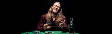 Photo pour Plan panoramique de l'homme barbu heureux dans des lunettes de vue tenant verre avec whisky près de jouer aux cartes isolées sur noir - image libre de droit