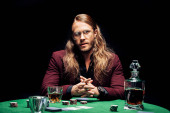 selective focus of man in eye glasses near playing cards on poker table isolated on black
