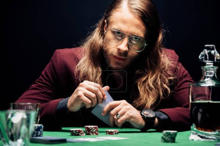 Photo pour KYIV, UKRAINE - AUGUST 20, 2019: selective focus of bearded man in eye glasses holding playing cards isolated on black - image libre de droit